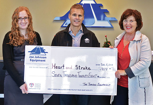 representatives from joe johnson equipment presenting a check to the heart and stroke foundation