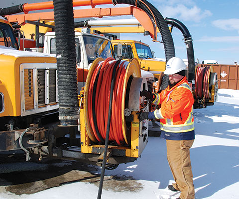 man spooling hose onto the front of a vac truck